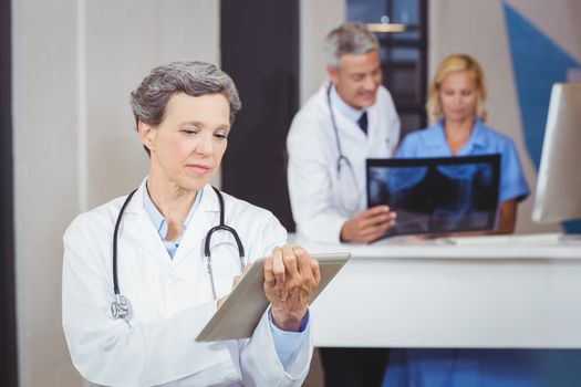 Female doctor using digital tablet with colleague checking X-ray