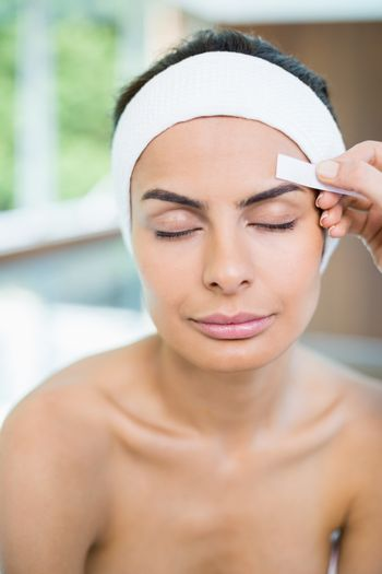 Close-up of woman with eyes closed while receiving face waxing