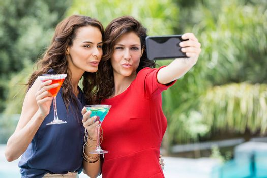 Happy friends taking self portrait while holding drinks at resort