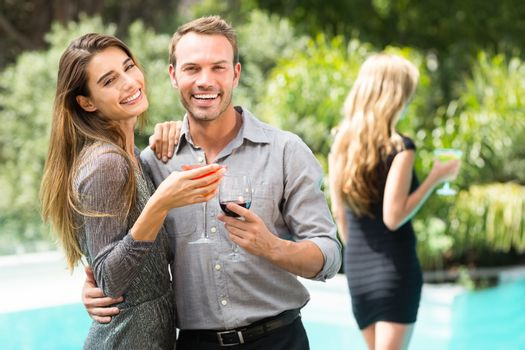 Couple drinking cocktail by swimming pool at party
