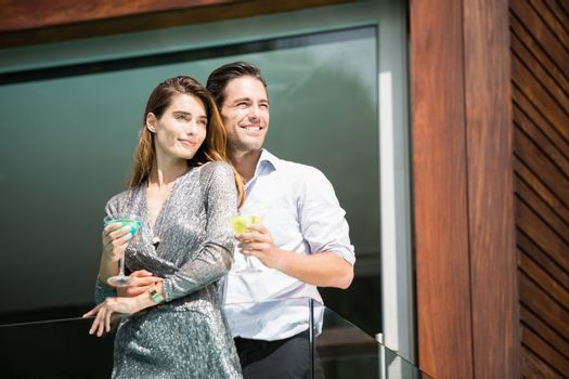 Couple with drinks standing in balcony at resort