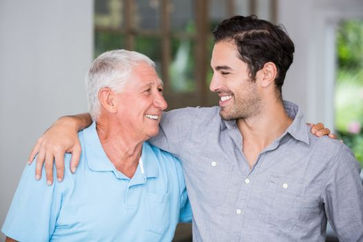 Smiling father and son with arm around