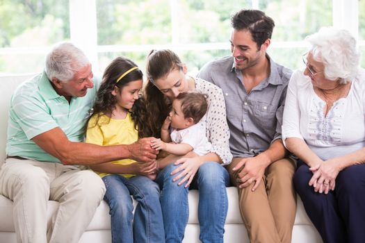 Smiling family playing with baby while sitting on sofa at home