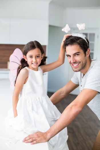 Portrait of smiling father with butterfly headband and daughter