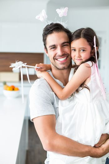 Portrait of father carrying daughter in fairy costume