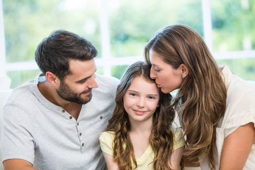 Close-up of mother kissing daughter while father watching them at home