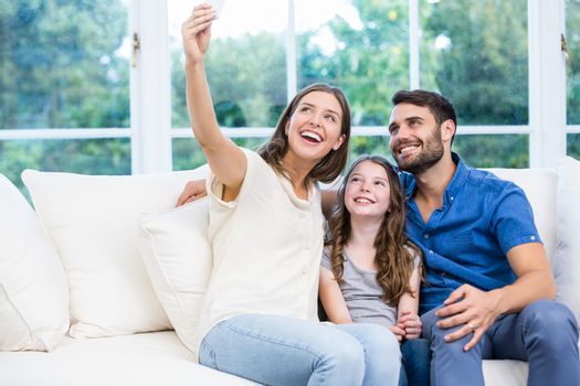 Family clicking selfies while sitting on sofa