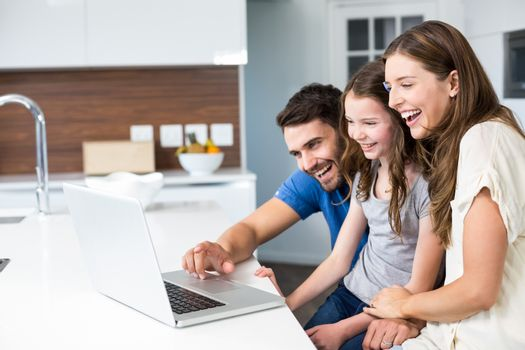 Happy family looking at laptop at home