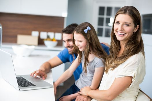 Portrait of woman with family using laptop at home