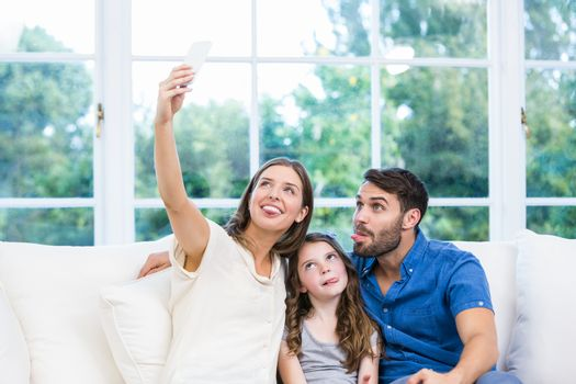Woman clicking selfie with family on sofa