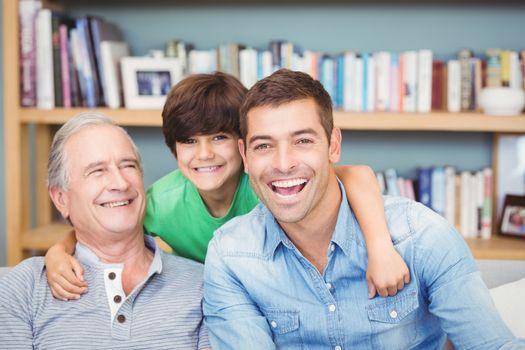 Portrait of happy multi genration family against bookshelf at home