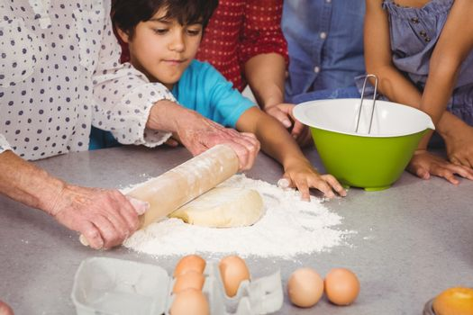 Grandmother with grandchildren using rolling pin
