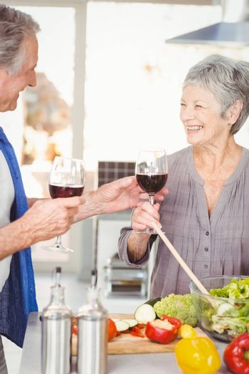 Happy senior man offering red wine to wife while standing in kitchen