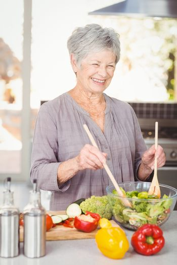 Happy senior woman tossing salad while standing in kitchen