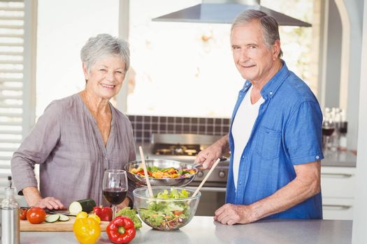 Portrait of happy senior couple preparing food while standing in kitchen