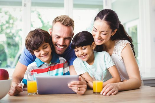 Smiling family using digital tablet at home