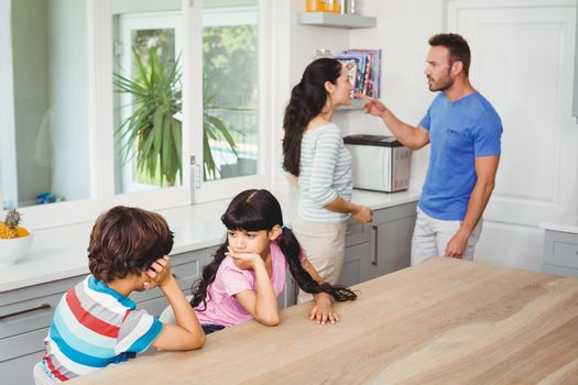 Children sitting at table with parents quarreling