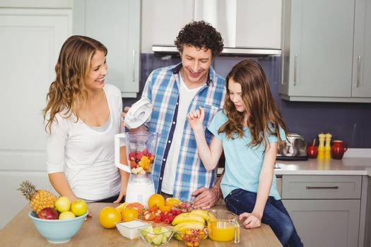 Smiling family preparing fruit juice at table in kitchen