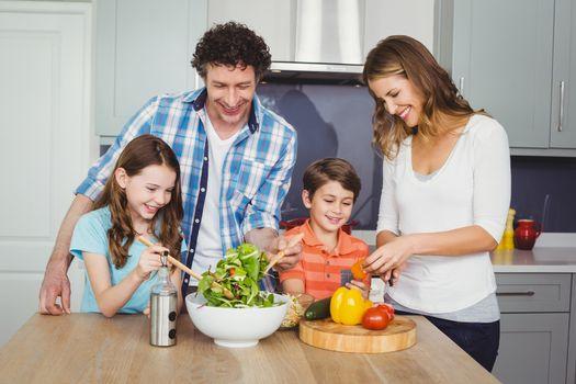 Happy family preparing vegetable salad in kitchen