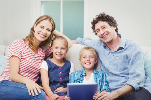 Portrait of happy family with digital tablet sitting on sofa at home