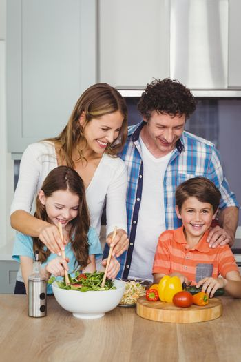 Happy family standing by table in kitchen at home