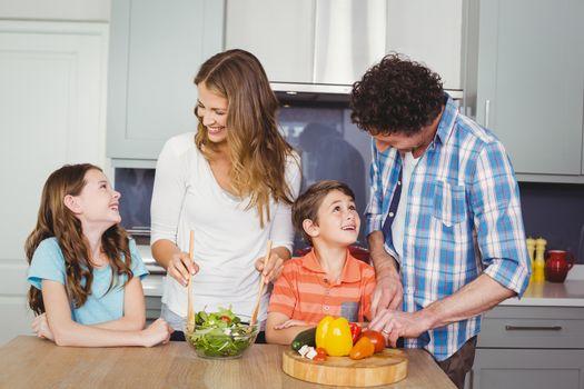 Smiling family preparing vegetable salad in kitchen