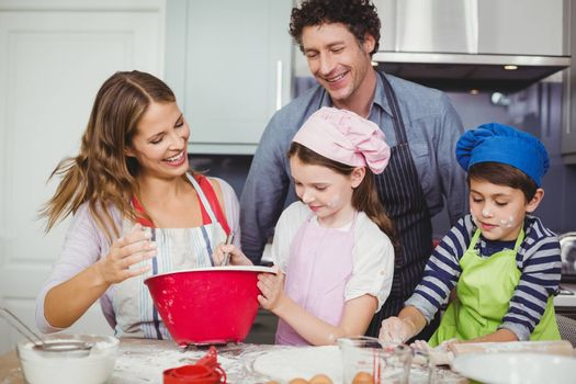 Smiling happy family cooking food in kitchen at home