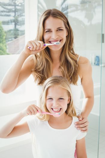 Portrait of smiling mother and daughter brushing teeth at home
