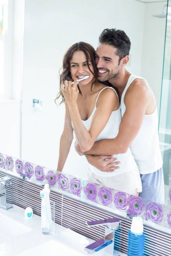 Reflection of wife brushing teeth while husband embracing her in bathroom
