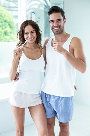 Portrait of happy young couple brushing teeth while standing in bathroom