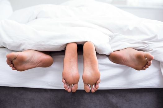 Low section of couple having sex on bed in room