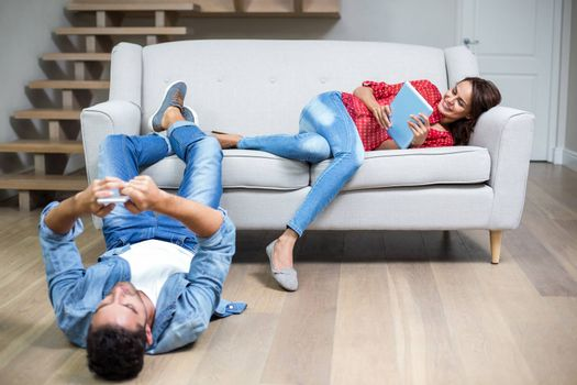 Happy couple using technology while relaxing at home