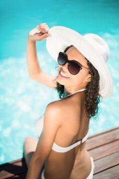 Beautiful woman wearing white bikini and hat sitting near pool on a sunny day