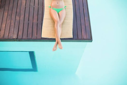 Beautiful woman in green bikini relaxing by poolside on a sunny day