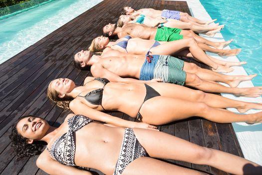 Group of friends in swimwear relaxing side by side near pool