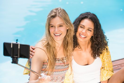 Beautiful women taking a selfie by swimming pool