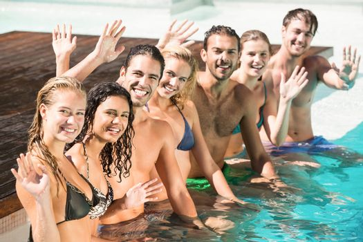 Portrait of friends waving hands in swimming pool