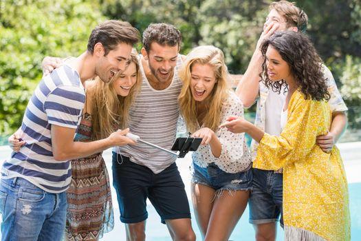 Group of friends taking a selfie near pool