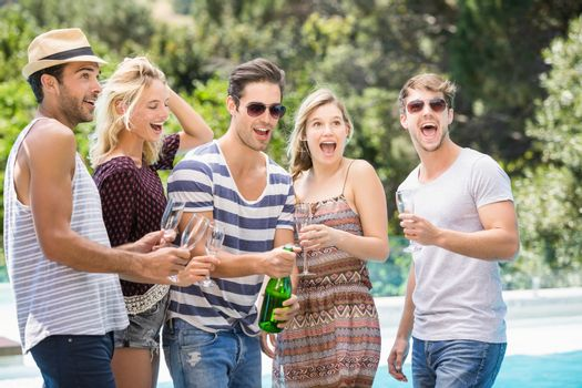 Group of friends popping a champagne bottle