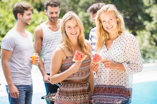 Young women smiling and having a slice of water melon