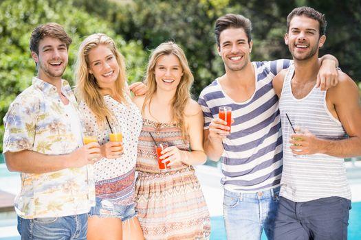 Portrait of friends having juice near pool