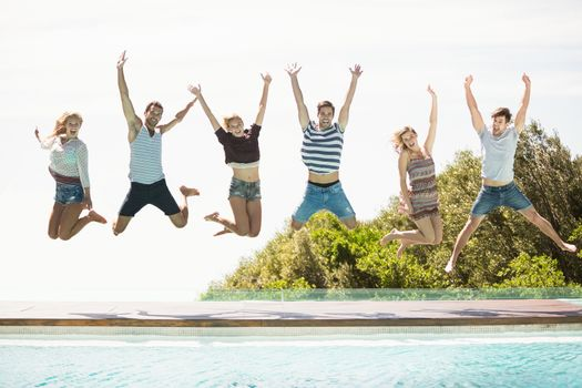 Group of friends jumping at poolside