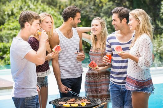 Happy friends preparing barbecue near pool