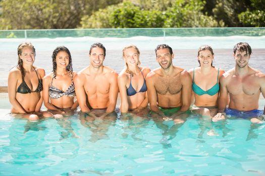 Portrait of friends sitting in swimming pool