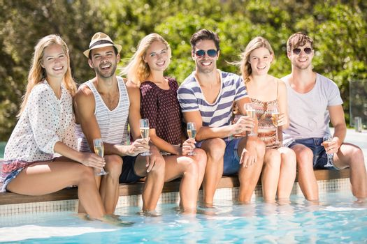 Group of friends sitting at poolside with glass of champagne