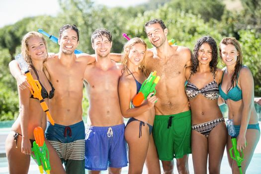 Happy friends standing with water guns
