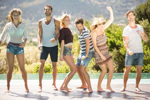 Group of friends dancing at poolside