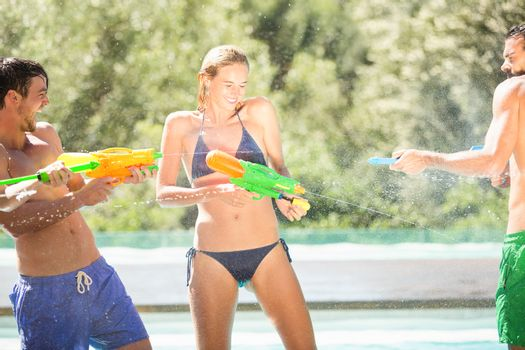 Happy friends doing water gun battle