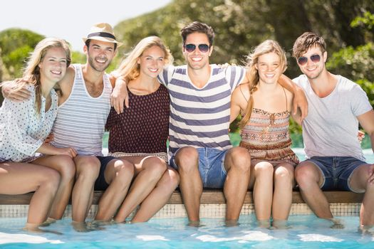 Group of friends sitting side by side at poolside