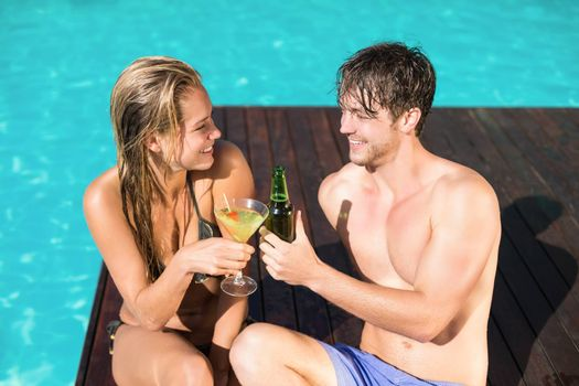 Young couple sitting at the swimming pool having drink